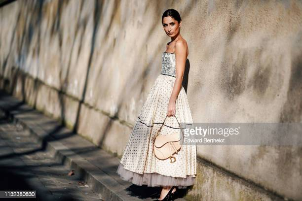 Geraldine Boublil wears a Dior pleated white off-shoulder dress with printed features, polka dots, a Dior Saddle bag, outside Dior, during Paris...