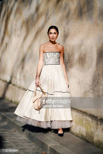 Geraldine Boublil wears a Dior pleated white offshoulder dress with printed features polka dots a Dior Saddle bag outside Dior during Paris Fashion...
