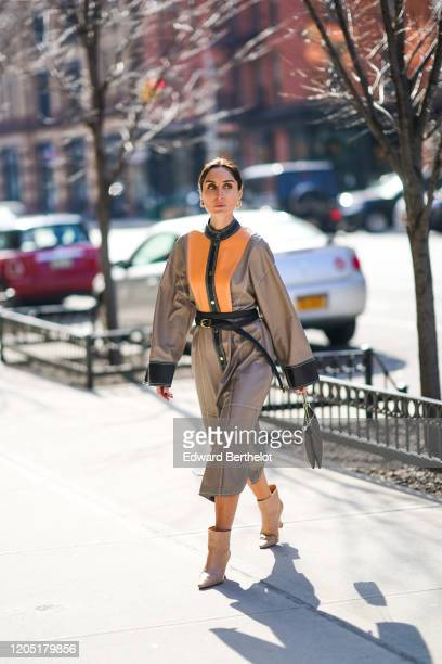 Geraldine Boublil wears a gray and orange coat/dress with buttons and large sleeves, a small black bag, a belt, pointy boots, outside Brock...