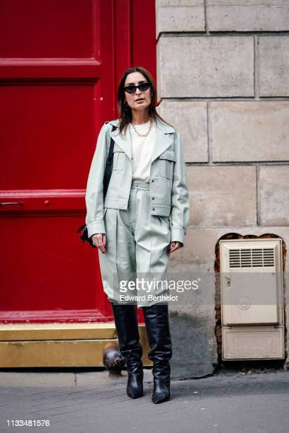 Geraldine Boublil wears a jacket a white top pale green pants black leather boots necklace sunglasses outside Thom Browne during Paris Fashion Week...