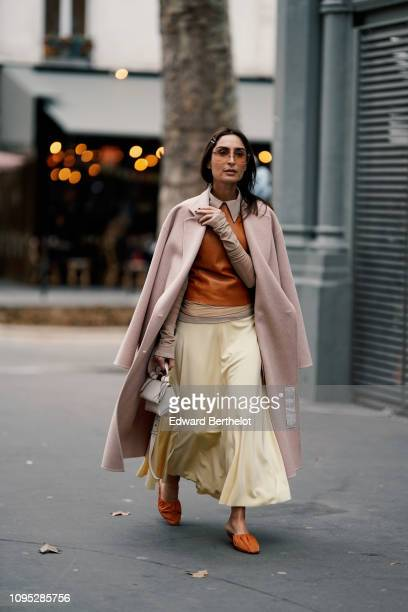 Geraldine Boublil wears a pink coat an orange top a pale yellow skirt orange shoes a white bag sunglasses hair pin outside Acne Studios during Paris...