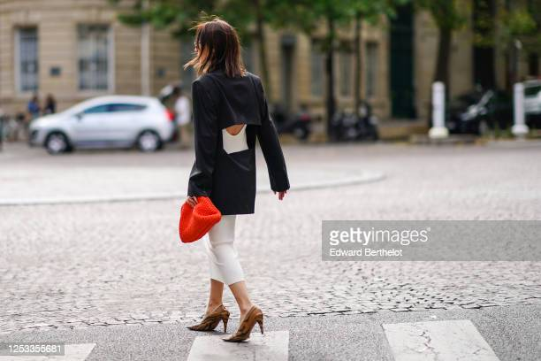 Geraldine Boublil wears a white dress from Basilika a Gauge 81 navy dark blue oversized blazer jacket with a large back cutout a red woven leather...