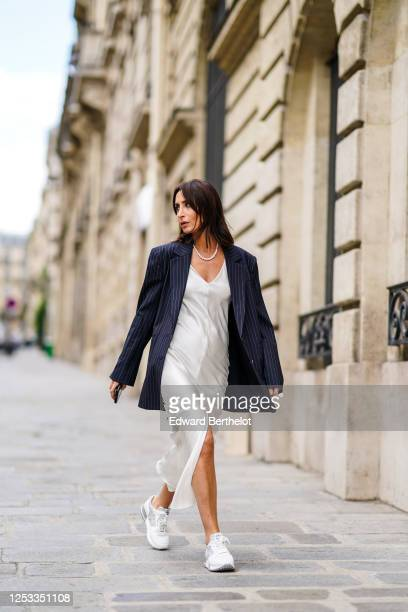 Geraldine Boublil wears a white pearl necklace from Coconut Love a dark navy blue striped oversized blazer jacket from Gauge 81 a white lustrous...