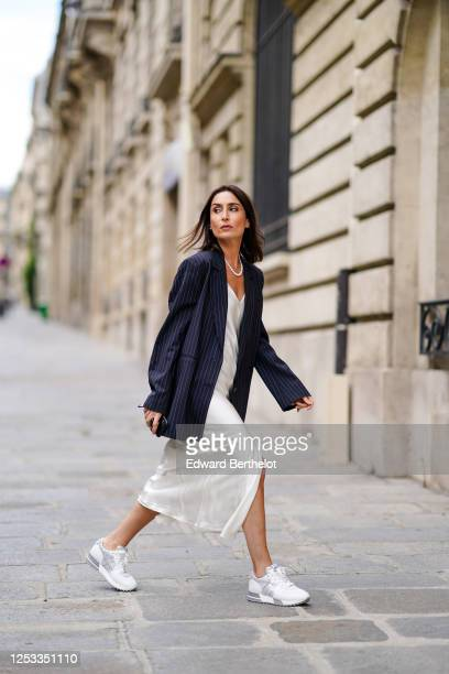 Geraldine Boublil wears a white pearl necklace from Coconut Love, a dark navy blue striped oversized blazer jacket from Gauge 81, a white lustrous...