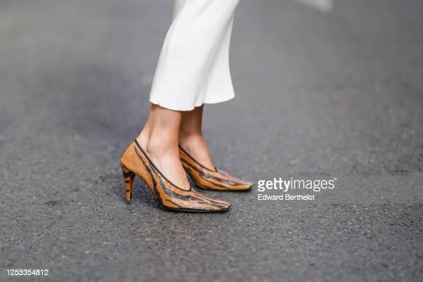 Geraldine Boublil wears Bottega Veneta brown and black zebra print pointy high heeled leather shoes on June 29 2020 in Paris France