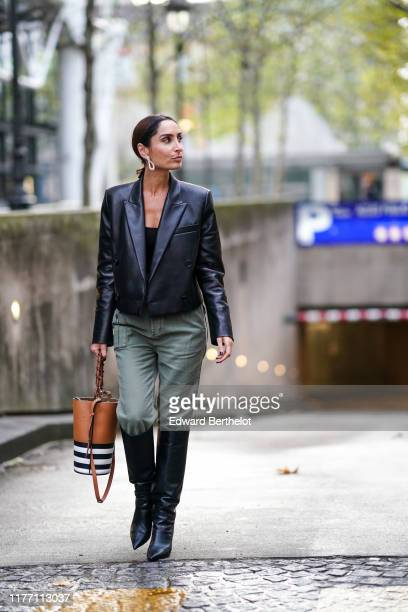 Geraldine Boublil wears earrings a black top a black leather jacket with shoulder pads a tancolor bag with white and black stripes khaki pants black...