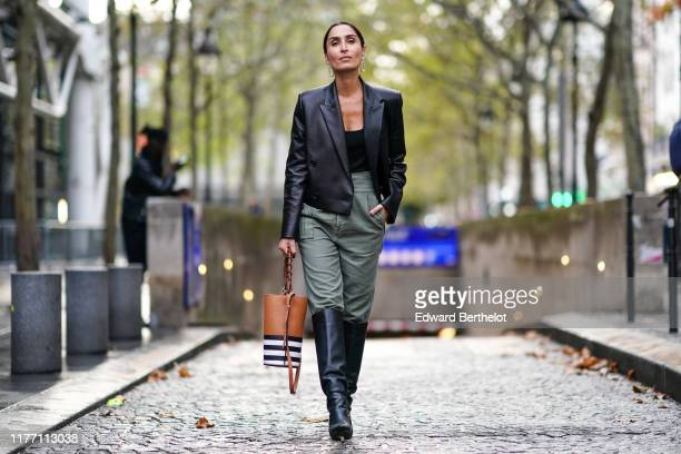Geraldine Boublil wears earrings, a black top, a black leather jacket with shoulder pads, a tan-color bag with white and black stripes, khaki pants,...