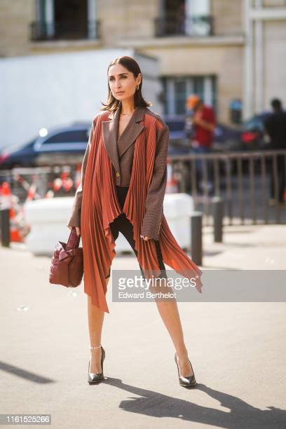 Geraldine Boublil wears earrings a brown checkered oversized jacket with rustcolor pleated panels black cycling shorts a brown quilted Acne Studios...