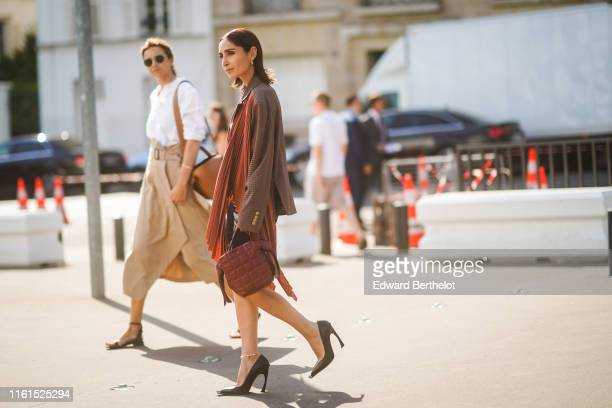 Geraldine Boublil wears earrings a brown checkered oversized jacket with rustcolor pleated panels a brown quilted Acne Studios bag an anklet black...