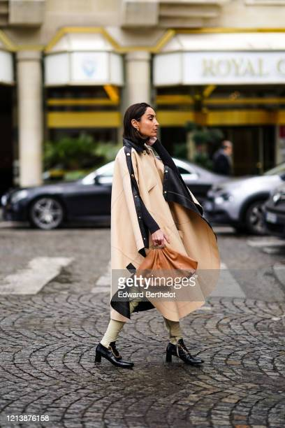 Geraldine Boublil wears earrings, a long leather black and beige poncho coat, a brown Bottega Veneta bag, black and white leather pointy shoes with...