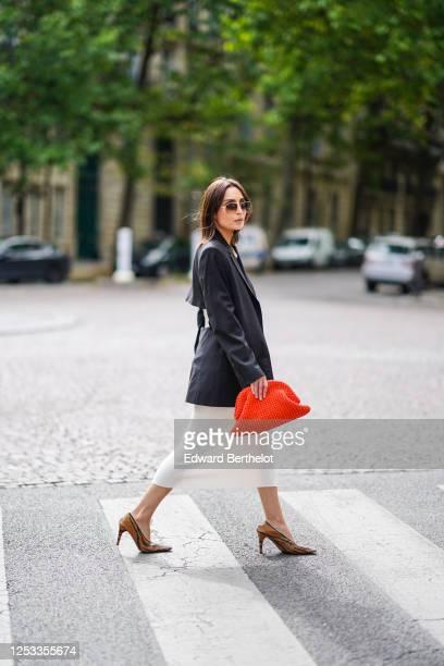 Geraldine Boublil wears Moscot sunglasses a white dress from Basilika a Gauge 81 navy dark blue oversized blazer jacket a red woven leather Bottega...