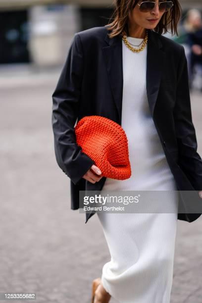 Geraldine Boublil wears Moscot sunglasses, a white dress from Basilika, a Gauge 81 navy dark blue oversized blazer jacket, a red woven leather...