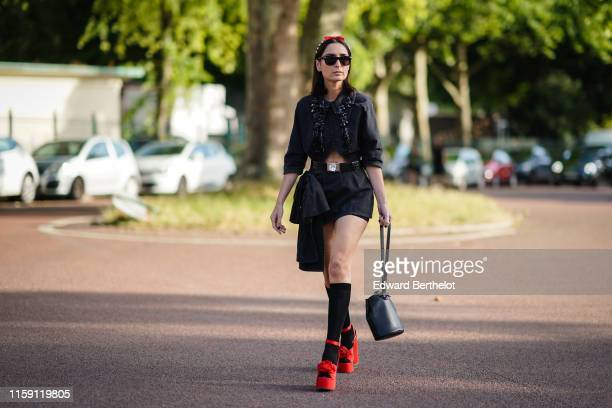 Geraldine Boublil wears sunglasses a black dress a belt a bag black socks red shoes with attached flowers outside Miu Miu Club 2020 on June 29 2019...