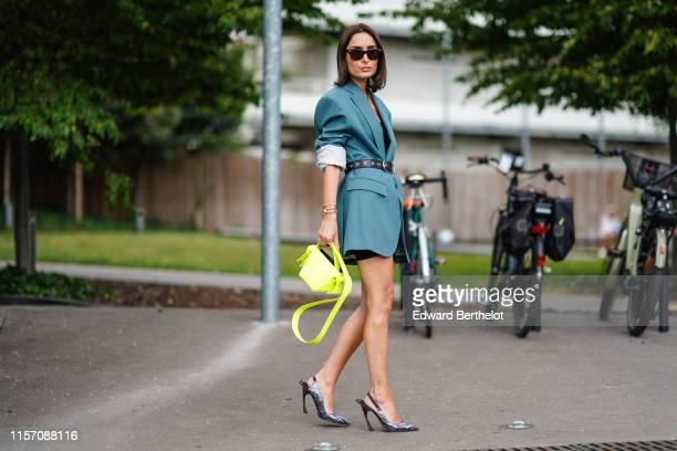 Geraldine Boublil wears sunglasses a blue blazer jacket dress a leather belt a black top shoes a neon yellow bag outside Acne Studios during Paris...