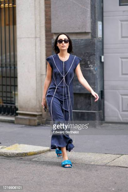 Geraldine Boublil wears sunglasses, a blue flowing ruffled jumpsuit with flare pants, blue quilted Bottega Veneta sandals, outside Sportmax, during...
