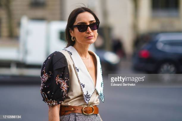 Geraldine Boublil wears sunglasses, a brown leather belt, a gray skirt, a low neck bejeweled top with puff shoulders, outside Miu Miu, during Paris...