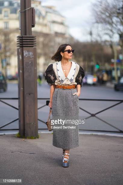 Geraldine Boublil wears sunglasses a brown leather belt a striped skirt a leather bag a low neck bejeweled top with puff shoulders outside Miu Miu...