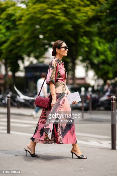 Geraldine Boublil wears sunglasses, a burgundy leather bag, a pink pleated dress with printed patterns, outside Paul Smith, during Paris Fashion Week...