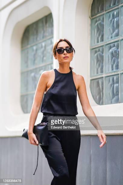 Geraldine Boublil wears sunglasses a dark navy blue silky lustrous tank top from Basilika metallic silver earrings from Bottega Veneta a Loewe black...