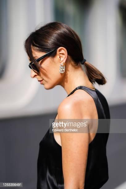 Geraldine Boublil wears sunglasses a dark navy blue silky lustrous tank top from Basilika metallic silver earrings from Bottega Veneta on June 29...