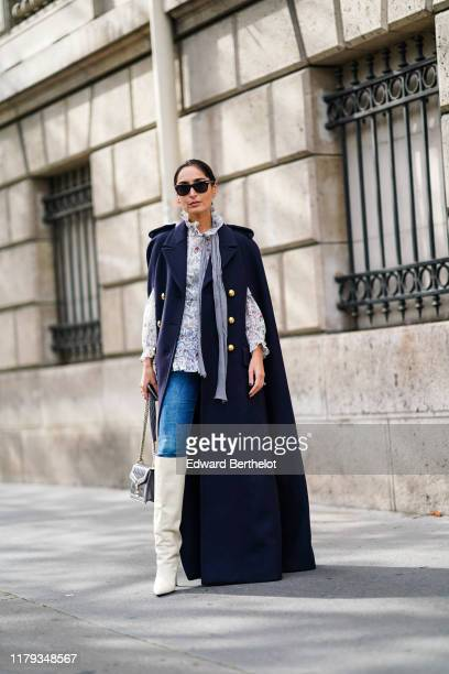 Geraldine Boublil wears sunglasses, a navy blue military long coat with golden buttons, blue denim jeans pants, a bag, white leather high boots, a...