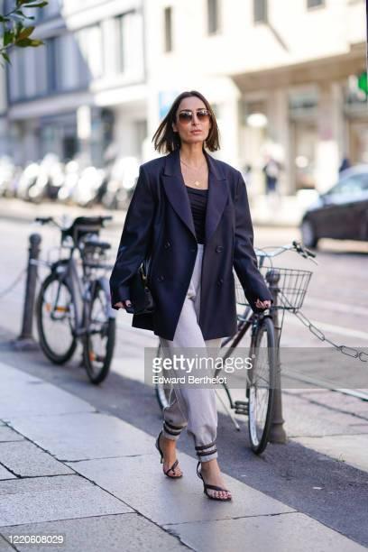 Geraldine Boublil wears sunglasses, a navy blue oversized blazer jacket, a black top, a necklace, gray pants, black shoes, outside Koche x Pucci,...