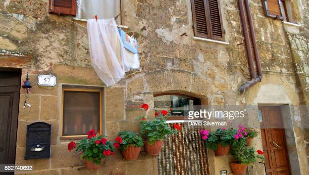 Geraniums and washing share a wall on July 22 2015 in the medieval village of Pitigliano in the Grosseto province of Tuscany Italy Tuscany is...