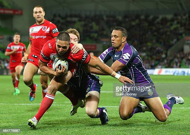 Gerard Beale of the Dragons breaks through a tackle by Tim Glasby and Will Chambers of the Storm during the round 6 NRL match between the Melbourne...