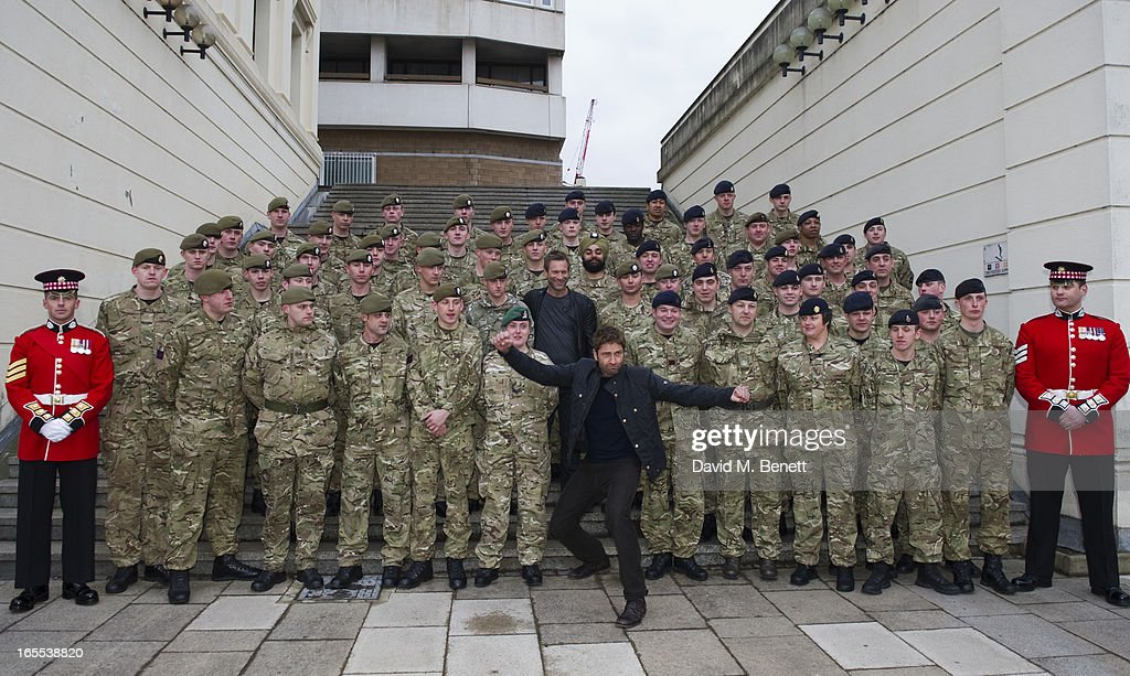 Gerard Butler and Aaron Eckhart pose with troops ahead of a special preview screening of Olympus Has Fallen, released in cinemas on April 17, at Wellington Barracks on April 4, 2013 in London, England.