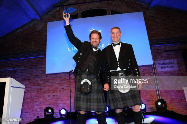 Gerard Butler and Magnus MacFarlane Barrow with award during the Cinema For Peace Gala at Westhafen Event Convention Center on February 23 2019 in...