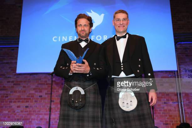 Gerard Butler and Magnus MacFarlane Barrow with award during the Cinema For Peace Gala at Westhafen Event & Convention Center on February 23, 2019 in...
