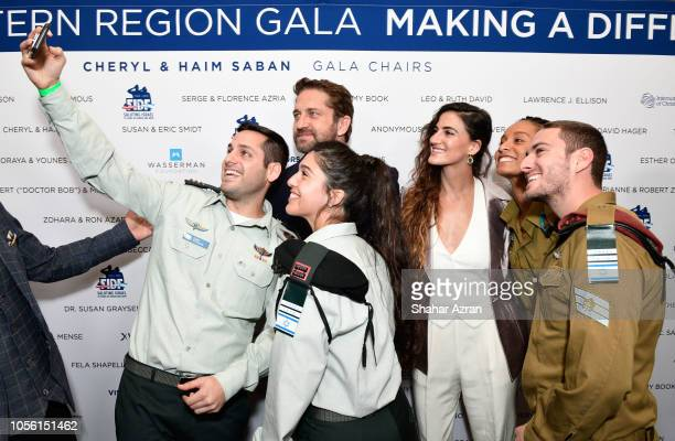 Gerard Butler and RonaLee Shimon and IDF soldiers take a selfie photo at Friends of The Israel Defense Forces Western Region Gala at The Beverly...
