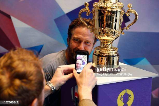 Gerard Butler poses for photos with The Webb Ellis Cup during day two of the Rugby World Cup 2019 Trophy Tour on March 22 2019 in Los Angeles...