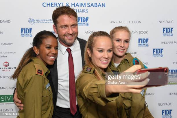 Gerard Butler with IDF soldiers at the FIDF Western Region Gala at The Beverly Hilton Hotel on November 2 2017 in Beverly Hills California