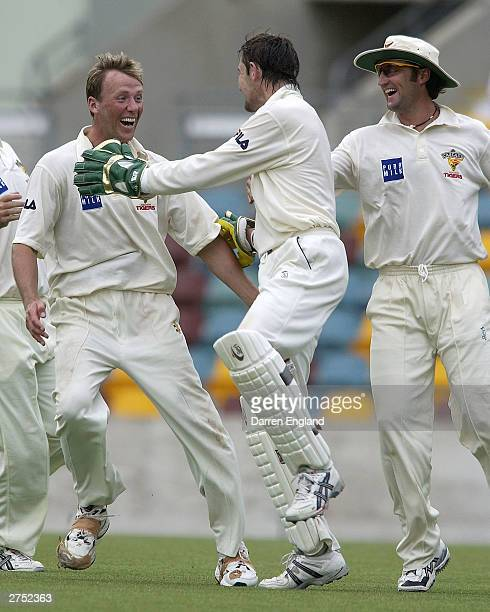 Gerard Denton of Tasmania celebrates with teammates after getting the wicket of Wade Seccombe of Queensland during the Pura Cup match between the...