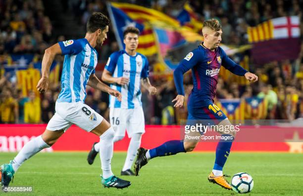 Gerard Deulofeu Lazaro of FC Barcelona is followed by Adrian Gonzalez Morales of Malaga CF during the La Liga 201718 match between FC Barcelona and...