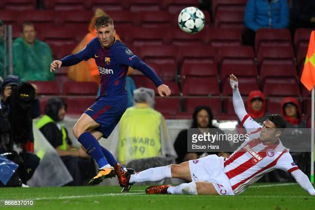 Gerard Deulofeu of Barcelona and Leonardo Koutris of Olympiakos compete for the ball during the UEFA Champions League group D match between FC...