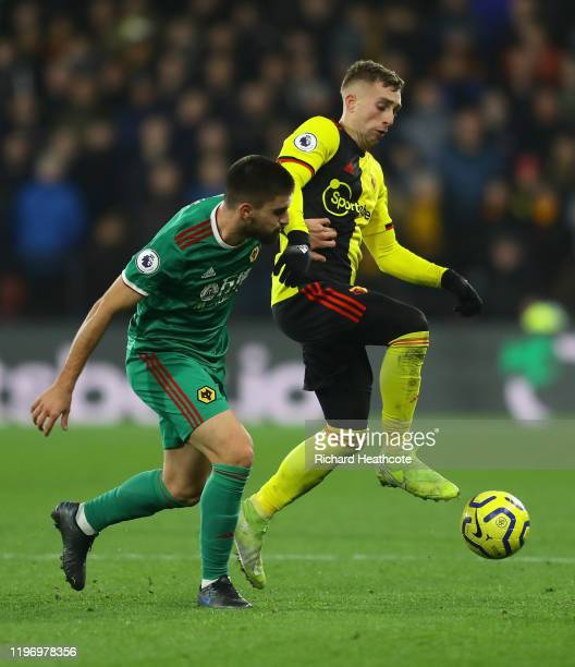 Gerard Deulofeu of Watford battles for possession with Ruben Neves of Wolverhampton Wanderers during the Premier League match between Watford FC and...