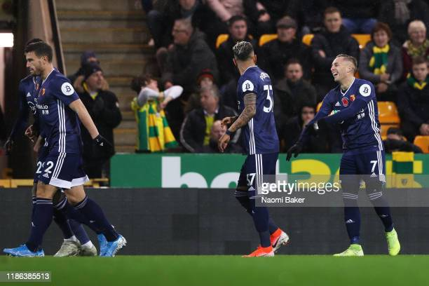 Gerard Deulofeu of Watford celebrates with his teammates after scoring his sides first goal during the Premier League match between Norwich City and...