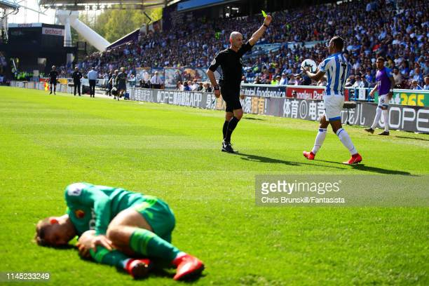 Gerard Deulofeu of Watford lies injured as Leandro Bacuna of Huddersfield Town is shown the yellow card by referee Roger East during the Premier...