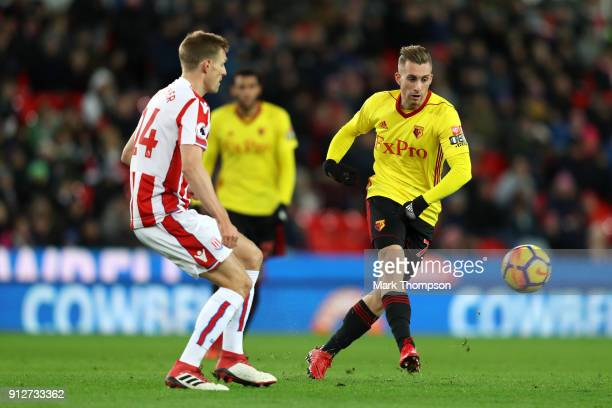 Gerard Deulofeu of Watford passes the ball under pressure from Darren Fletcher of Stoke City during the Premier League match between Stoke City and...