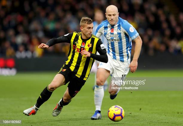 Gerard Deulofeu of Watford runs with the ball under pressure from Aaron Mooy of Huddersfield Town during the Premier League match between Watford FC...