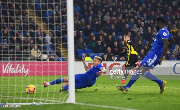 Gerard Deulofeu of Watford scores his team's second goal as Joe Bennett of Cardiff City fails to clear during the Premier League match between...
