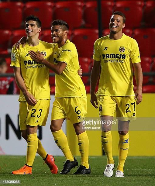 Gerard Moreno Balaguer of Villarreal CF celebrates with Jonathan Dos Santos of Villarreal CF and Tano Bonnin of Villarreal CF after scoring the...