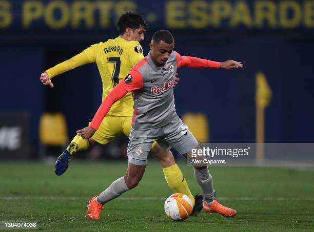 Gerard Moreno of Villarreal battles for possession with Antoine Bernede of Red Bull Salzburg during the UEFA Europa League Round of 32 match between...