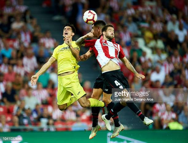 Gerard Moreno of Villarreal CF competes for the ball with Inigo Martinez and Yuri Berchiche of Athletic Club during the La Liga match between...