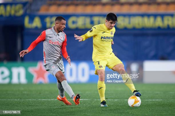 Gerard Moreno of Villarreal CF controls the ball under pressure from Antoine Bernede of RB Salzburg during the UEFA Europa League Round of 32 second...