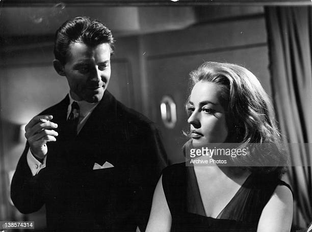 Gerard Philipe having a cigarette while looking at Jeanne Moreau in a scene from the film 'Les Liaisons Dangereuses', 1959.