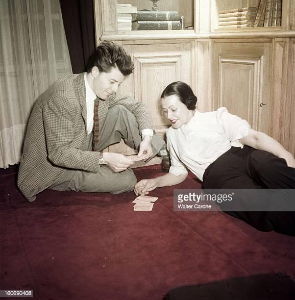 Gerard Philippe And His Mother Gérard PHILIPE se faisant tirer les cartes par sa mère Minou assis par terre dans le salon