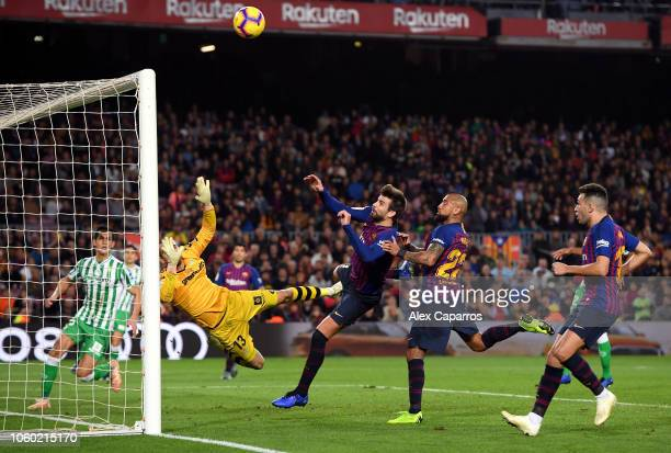 Gerard Pique and Arturo Vidal of Barcelona jump for the ball during the La Liga match between FC Barcelona and Real Betis Balompie at Camp Nou on...